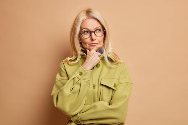 Linda mulher atraente de meia-idade segura o queixo e pensa profundamente, desvia o olhar vestido com uma jaqueta da moda e pondera sobre algo importante.