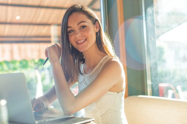 Linda mulher atraente no café com um laptop tendo uma pausa para café