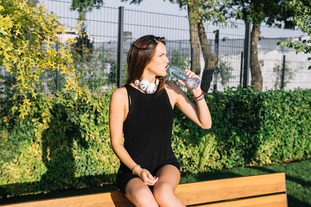 Linda mulher bebendo água no parque