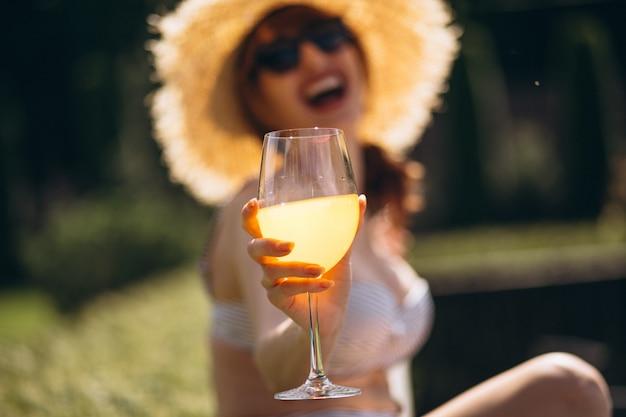 Linda mulher bebendo suco em fato de banho