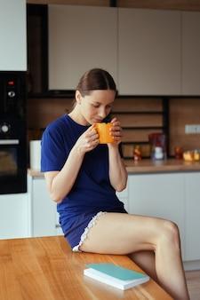 Linda mulher bebendo uma xícara de chá na cozinha