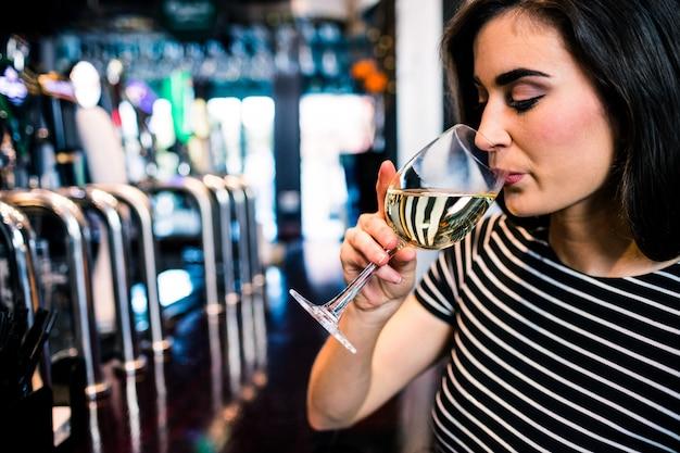 Linda mulher bebendo vinho em um bar