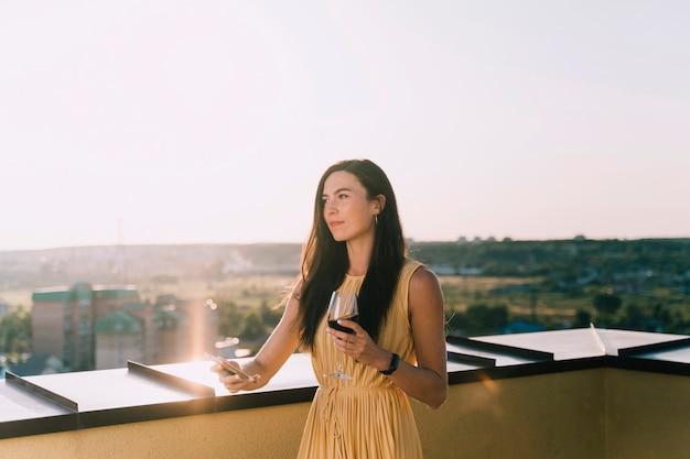 Linda mulher bebendo vinho no telhado à luz do sol