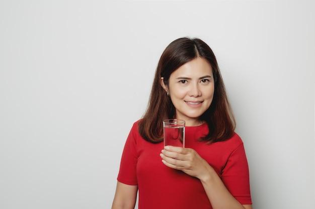 Linda mulher beber água de vidro