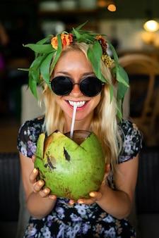 Linda mulher beber coco no café tropical