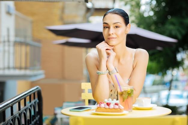 Linda mulher. bela jovem sentada à mesa do café com uma sobremesa deliciosa na frente dela e parecendo calma