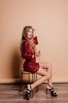Linda mulher branca com elegantes sapatos de salto alto, sentada na parede bege e bebendo champanhe