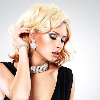 Linda mulher branca com penteado encaracolado e pulseira prateada - posando no estúdio