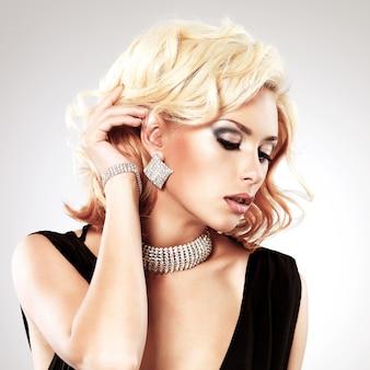 Linda mulher branca com penteado encaracolado posando no estúdio