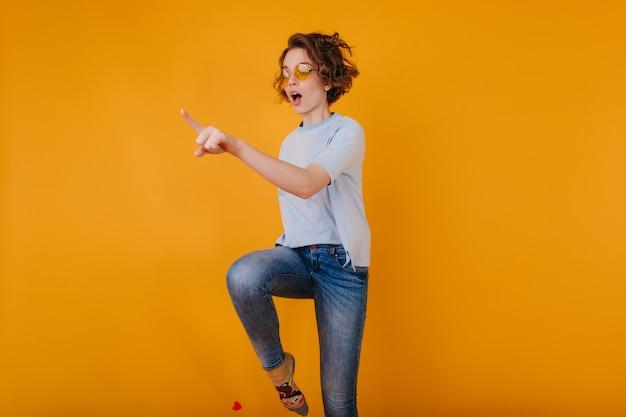 Linda mulher branca em calças jeans da moda pulando no espaço amarelo