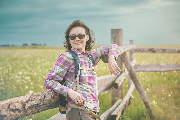 Linda mulher branca em óculos de sol fica em prado perto de cerca de pastagem num dia ensolarado de verão.