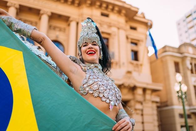 Linda mulher brasileira vestindo fantasia colorida de carnaval e a bandeira do brasil durante o desfile de carnaval na cidade.