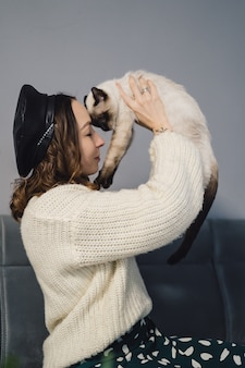 Linda mulher brincando com gato siamês
