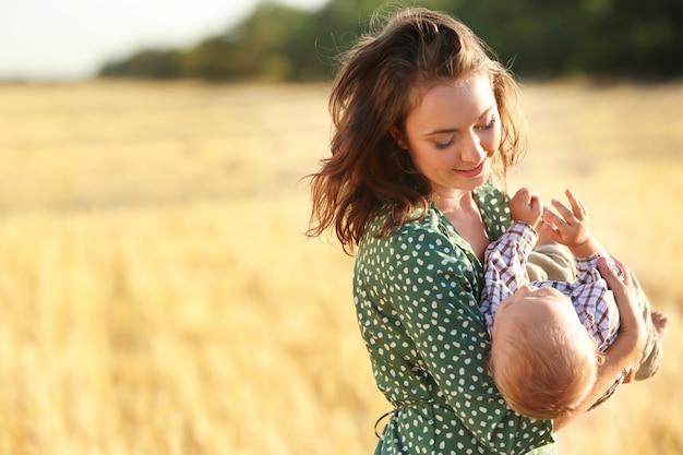 Linda mulher brincando com seu filho pequeno no campo de trigo num dia de verão