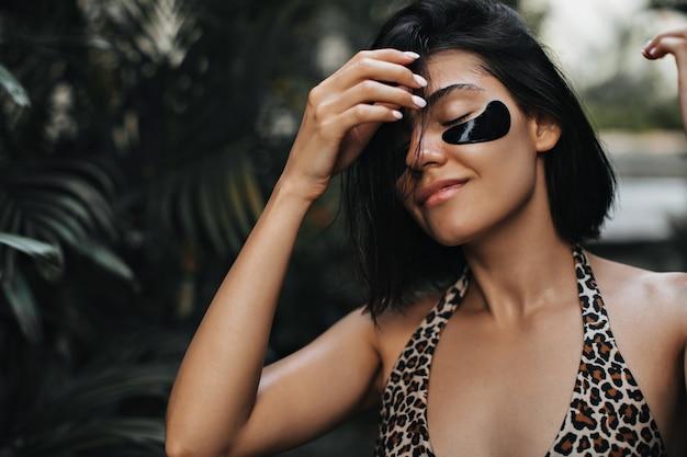 Linda mulher bronzeada aproveitando as férias no resort. mulher atraente com tapa-olhos tocando o cabelo no fundo da natureza.