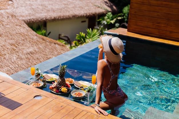 Linda mulher bronzeada caucasiana de biquíni e chapéu de palha com café da manhã flutuante na villa de estilo bali de luxo incrível em dia de sol na piscina, fundo tropical.