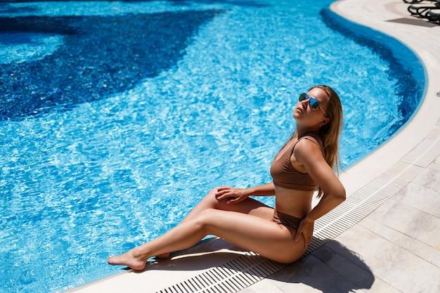 Linda mulher bronzeada está relaxando na piscina. jovem sexy em maiô bege em um dia ensolarado de verão à beira da piscina