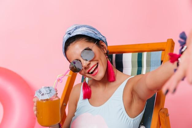 Linda mulher bronzeada posando com um copo de coquetel