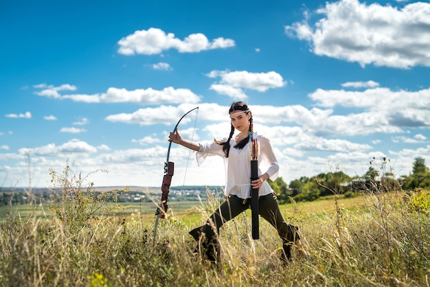 Linda mulher caçadora com arco brincando como um índio americano nativo ao ar livre