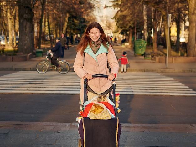 Linda mulher caminhando no parque da cidade com um gato em cobertor sentado na carruagem de bebê