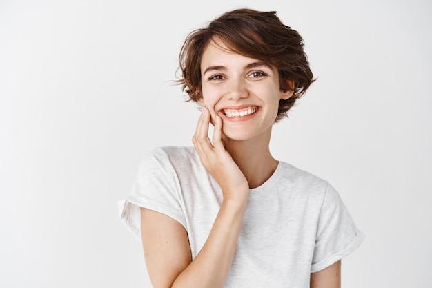 Linda mulher cândida com cabelo curto e sem maquiagem, tocando a pele limpa do rosto e sorrindo, em pé com uma camiseta na parede branca