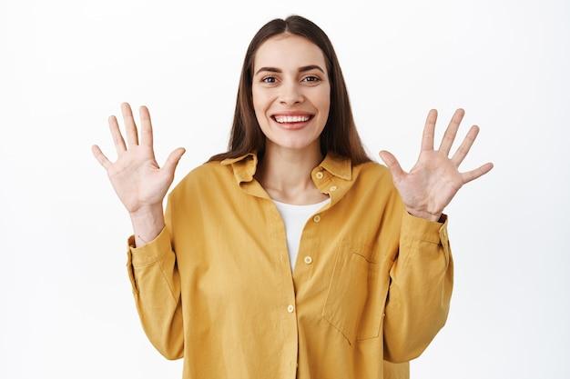 Linda mulher cândida mostrando as mãos vazias, levantando os braços em sinal de rendição e sorrindo feliz, de pé positivo contra uma parede branca