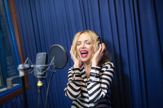 Linda mulher cantando em um estúdio de gravação