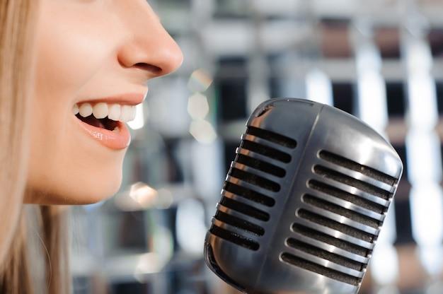 Linda mulher cantando no palco ao lado do microfone.