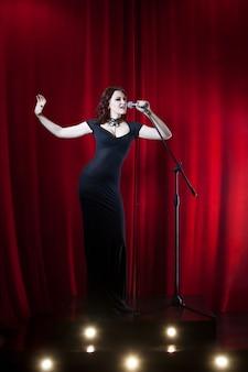 Linda mulher cantando no palco.