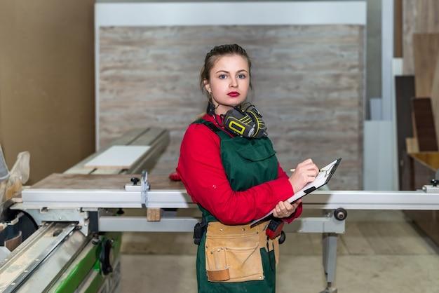 Linda mulher carpinteira fazendo algumas anotações no papel