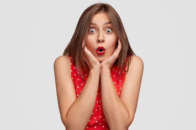 Linda mulher caucasiana abre a boca amplamente, prende a respiração, mantém a boca arredondada, segura o queixo com as duas mãos