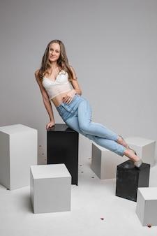 Linda mulher caucasiana com aparência charmosa se senta sobre cubos brancos e olha para a câmera, foto em branco