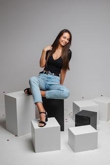 Linda mulher caucasiana com aparência charmosa sentada em um cubo branco e aparência, imagem isolada na parede branca