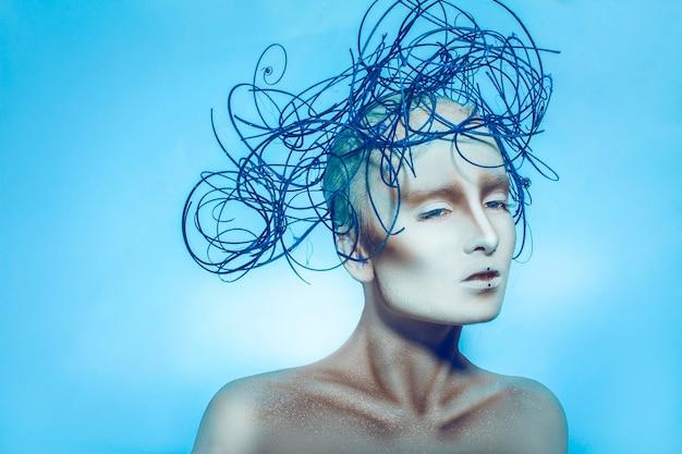 Linda mulher caucasiana com arte corporal em fundo azul