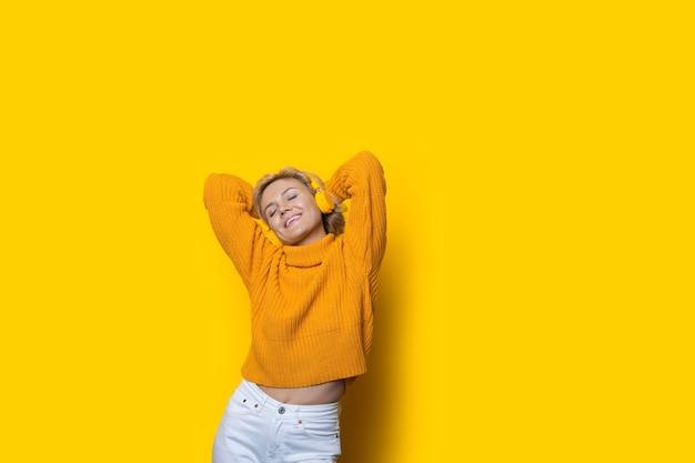 Linda mulher caucasiana com cabelo loiro ouvindo música com fones de ouvido na parede amarela de um estúdio com espaço livre