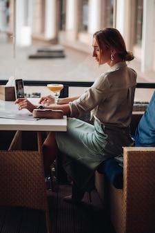 Linda mulher caucasiana com cabelo loiro tira uma foto de si mesma com um coquetel em um café
