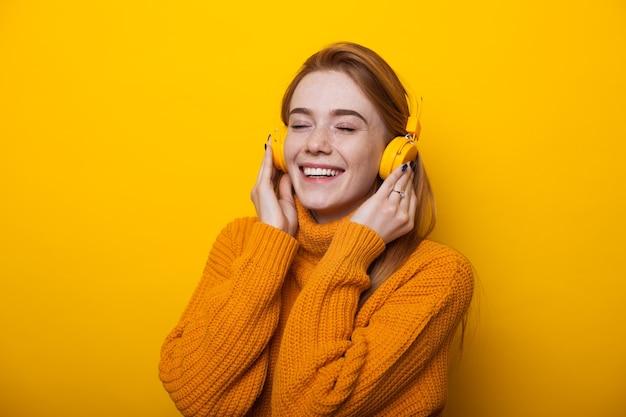Linda mulher caucasiana com cabelo ruivo e sardas ouvindo música usando fones de ouvido em uma parede amarela