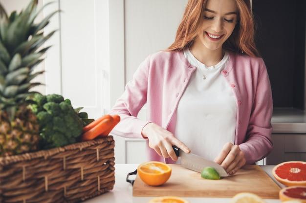 Linda mulher caucasiana com cabelo ruivo e sardas sorrindo enquanto corta um limão na cozinha com uma faca