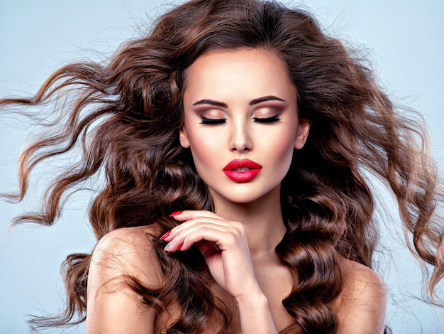 Linda mulher caucasiana com cabelos cacheados castanhos compridos. retrato de uma jovem adulta. rosto sexy de uma senhora atraente posando no estúdio sobre fundo cinza.