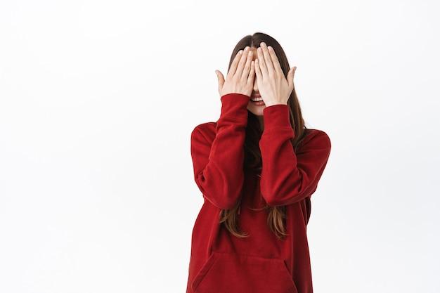 Linda mulher caucasiana com capuz vermelho cobrindo o rosto e os olhos com as palmas das mãos, sorrindo, esperando pela surpresa, brincando de esconde-esconde, encostada na parede branca
