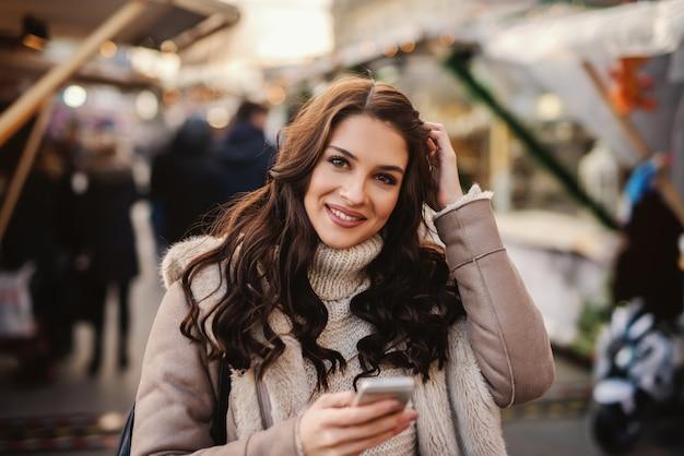 Linda mulher caucasiana com longos cabelos castanhos em pé na rua no frio, segurando um telefone inteligente