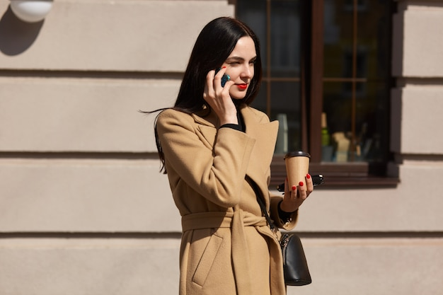 Linda mulher caucasiana, com longos cabelos escuros falando por telefone