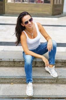 Linda mulher caucasiana com óculos está sentada na rua em uma escadaria lotada da cidade e smil ...