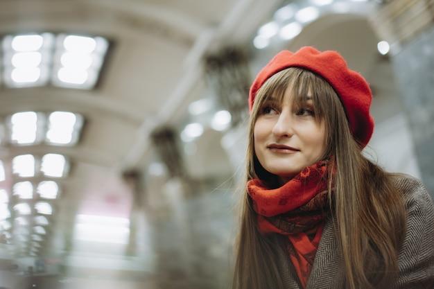 Linda mulher caucasiana com um casaco quente boina e lenço sentada sozinha no metrô de são petersburgo