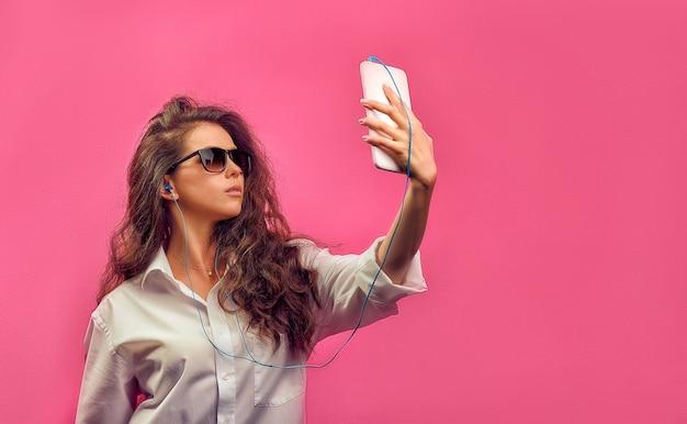 Linda mulher caucasiana com uma camisa branca de óculos com fones de ouvido, segurando um tablet branco nas mãos e faz selfie foto em uma parede rosa brilhante.