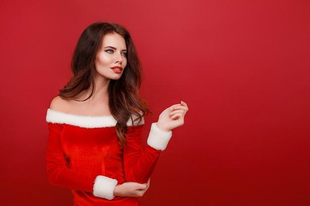 Linda mulher caucasiana com vestido de papai noel vermelho sobre fundo vermelho studio