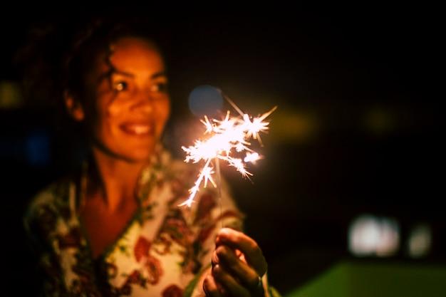 Linda mulher caucasiana comemora com brilhos de luz à noite
