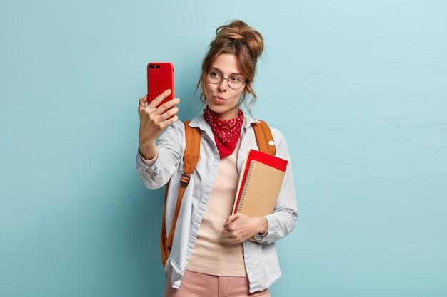 Linda mulher caucasiana de cabelos escuros faz selfie retrato com celular, mantém os lábios fechados, carrega caderno e mochila nas costas