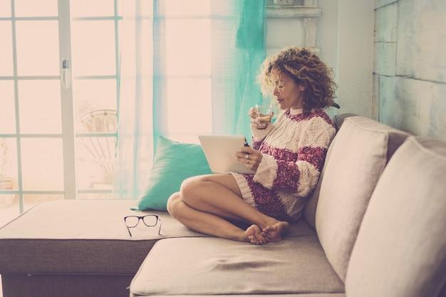 Linda mulher caucasiana de meia-idade com cabelo encaracolado, trabalhando em casa e relaxando no sofá com um tablet e internet