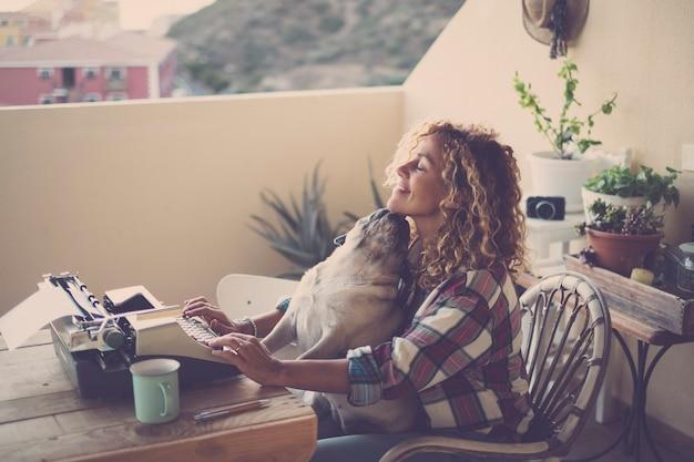 Linda mulher caucasiana de meia-idade usa uma velha máquina de escrever vintage como uma blogueira moderna no papel, enquanto seu adorável melhor amigo pug a beija com o conceito de amizade